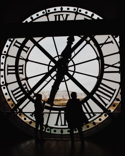 Silhouette man standing against wall clock