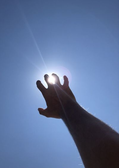 Low angle view of hand against clear blue sky