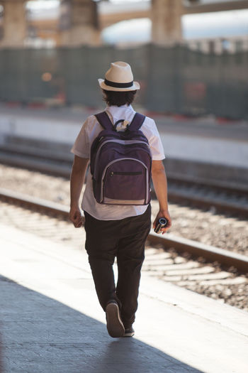 Rear view of man walking on railway platform