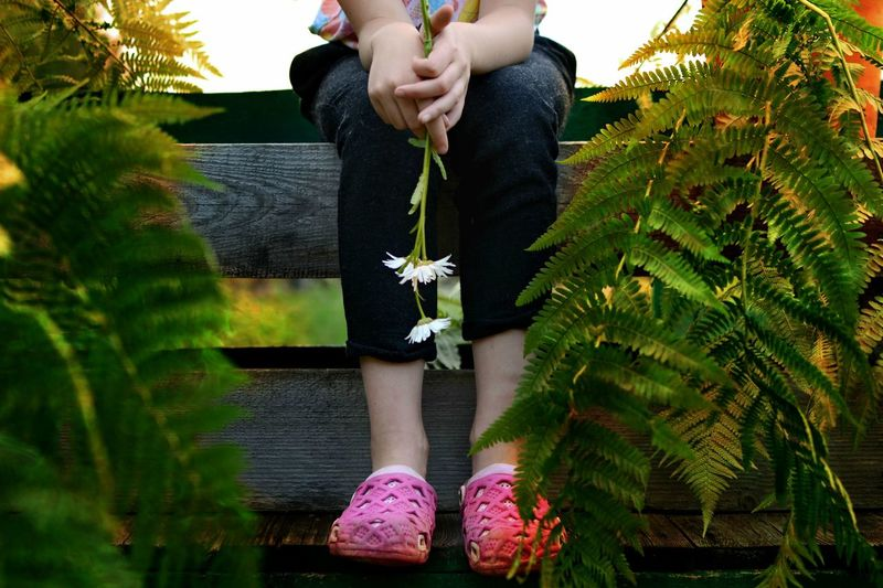 Low section of girl standing by flower tree