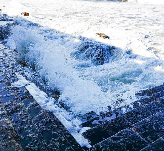Aerial view of sea waves splashing on land
