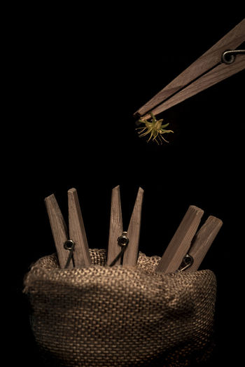 Close-up of wicker basket on table against black background