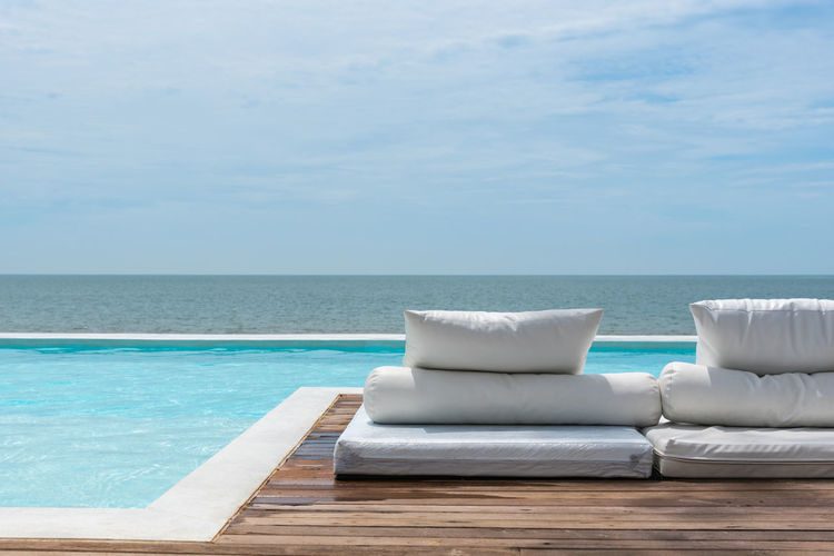 Lounge chairs by infinity pool against sea and sky during sunny day