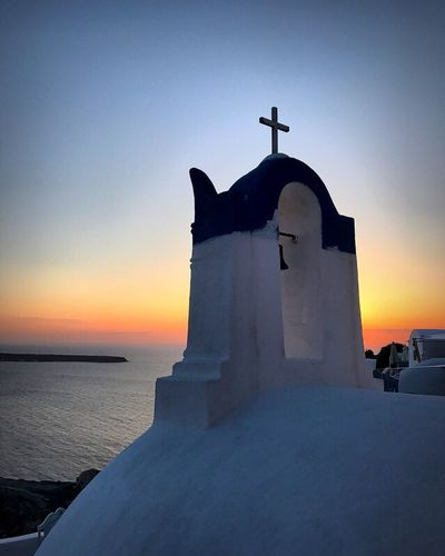 Oia sunset. Religion Sunset Spirituality Built Structure Architecture Place Of Worship Cross Sea No People Outdoors Building Exterior Sky Nature Beauty In Nature Clear Sky Horizon Over Water Whitewashed Bell Tower Scenics Day Santorini, Greece Blueandwhite Architecture Cross Sunset_collection