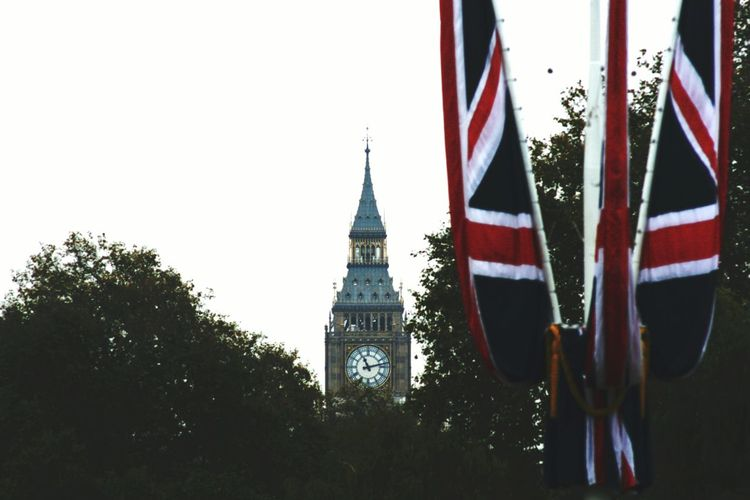 Low angle view of flags with buildings in background