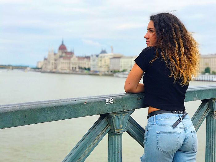 Young Woman Standing By Danube River On Bridge In City