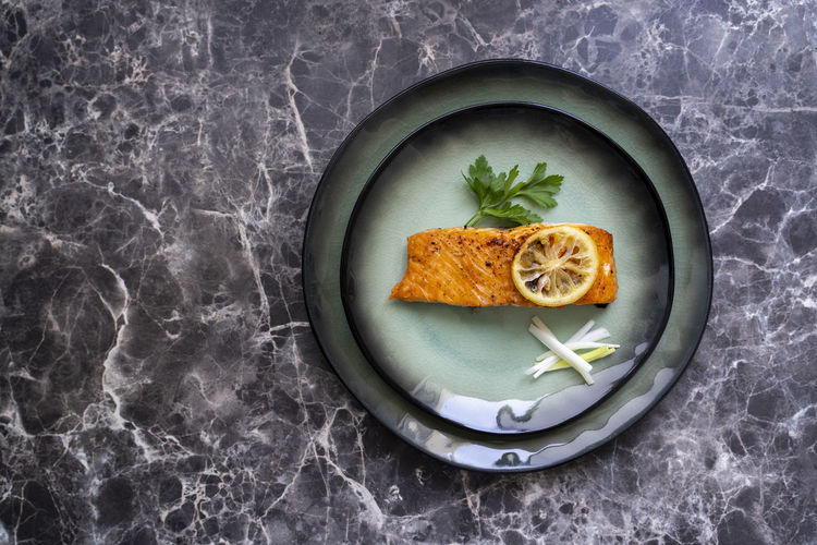High angle view top view of salmon fish fillet cooked with different spices and served on plate.