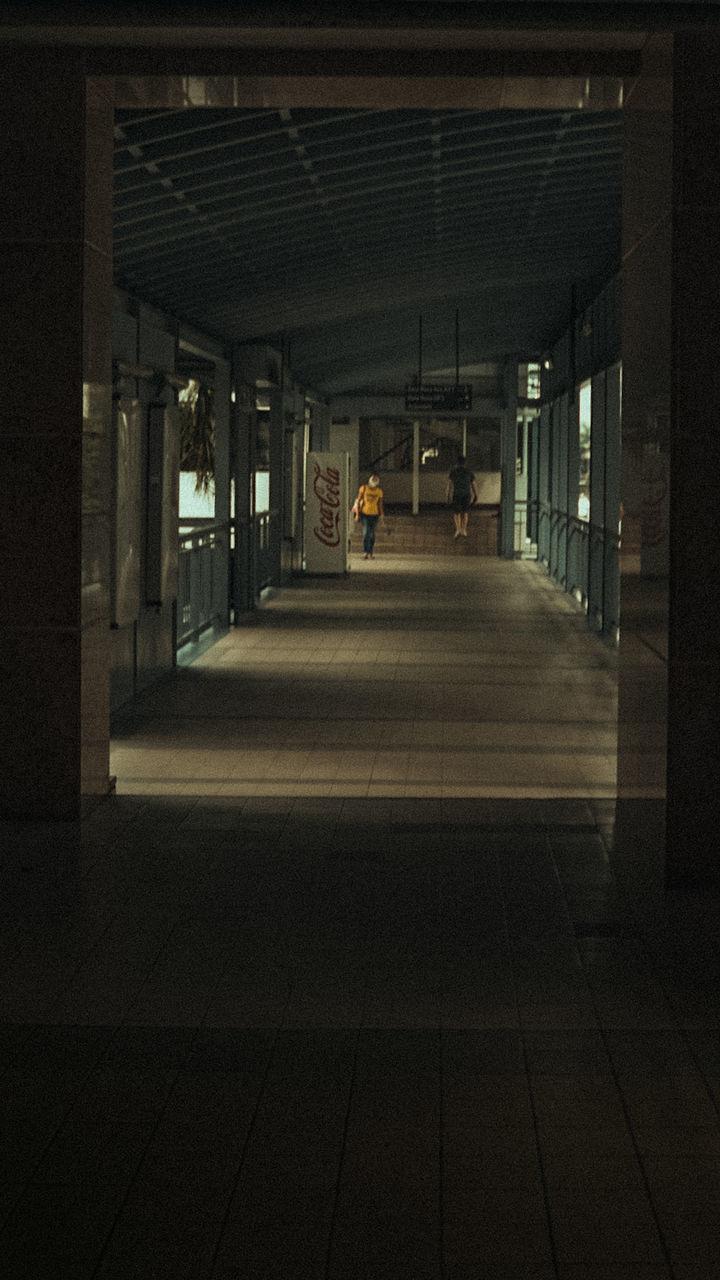 MAN WALKING IN ILLUMINATED BUILDING CORRIDOR
