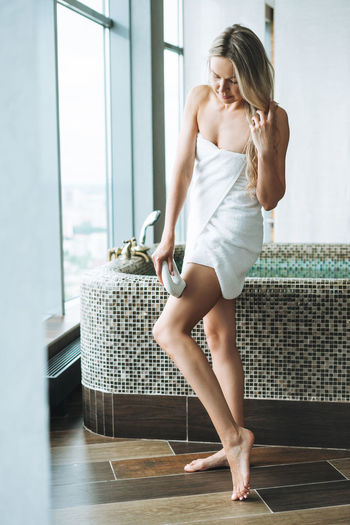 Young blonde woman in white towel does body massage with microcurrent home massager in bathroom
