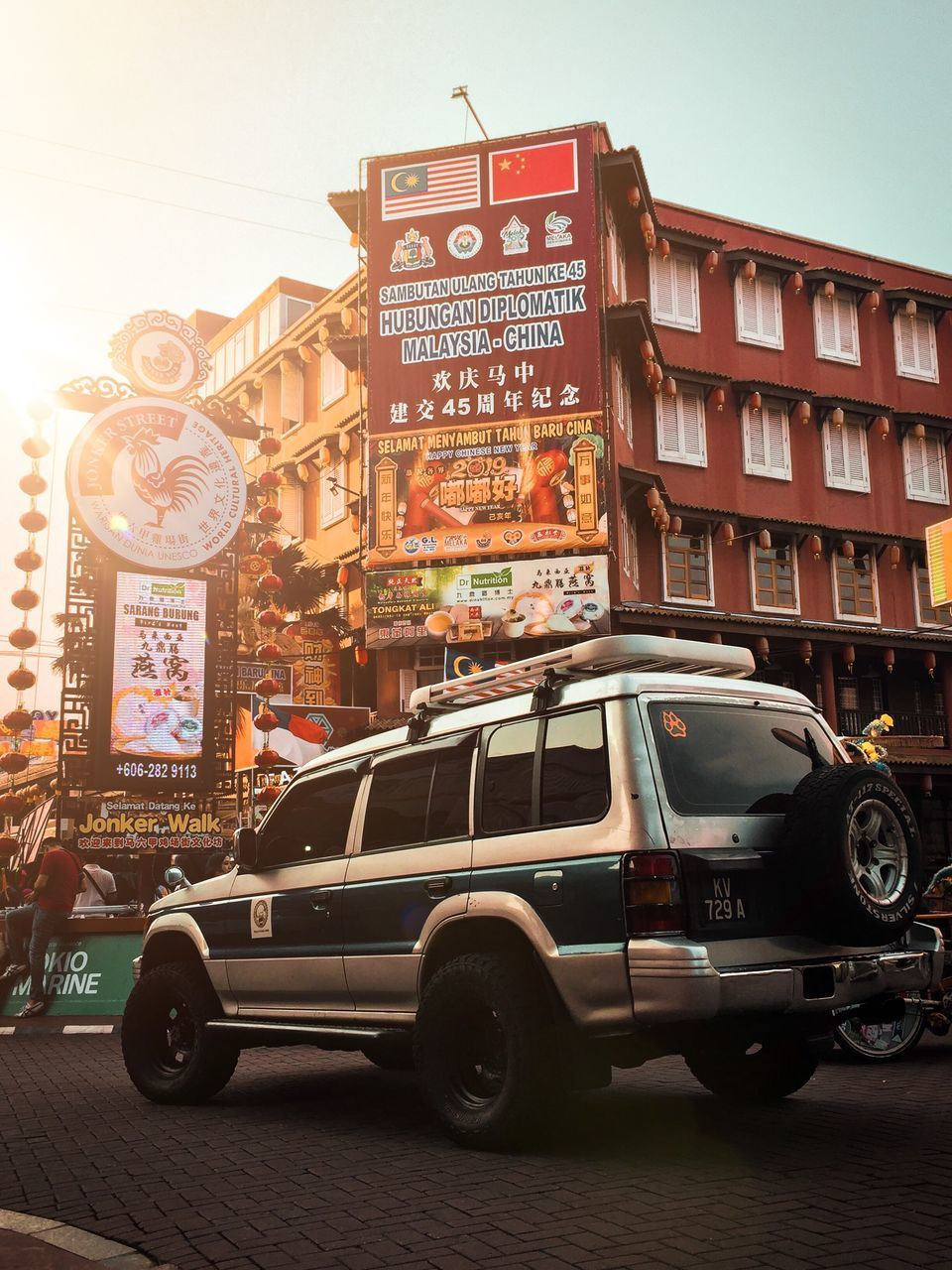 building exterior, architecture, mode of transportation, transportation, city, built structure, car, motor vehicle, land vehicle, street, text, city street, communication, western script, sky, road, city life, building, sign, script