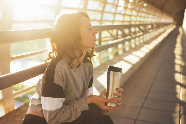 Thoughtful female athlete with bottle sitting on footbridge during sunset