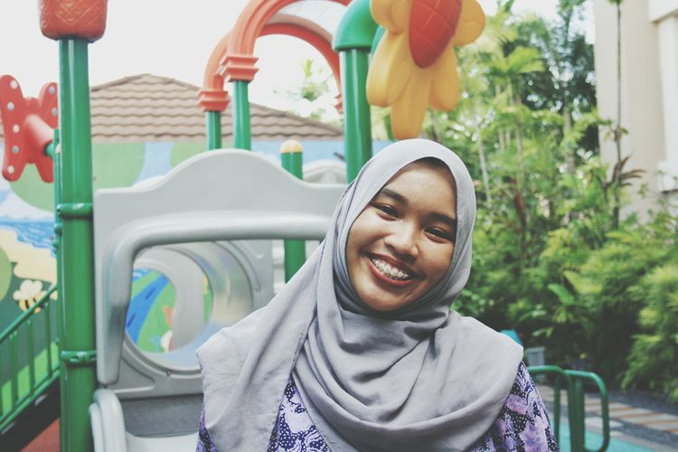 Portrait of smiling young woman wearing hijab at playground