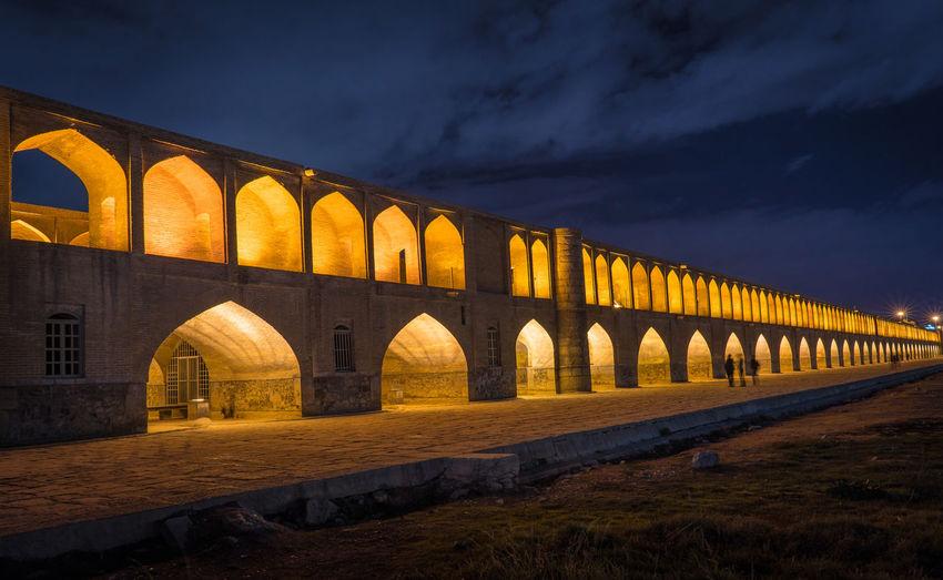 Arch bridge against sky at night