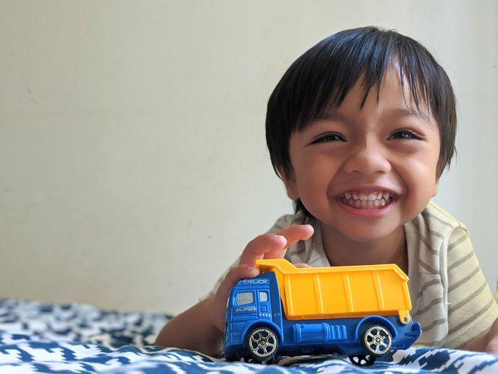 Portrait of happy boy with toy car