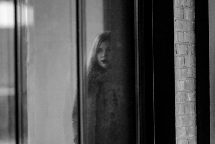 Reflection of beautiful woman falling on window