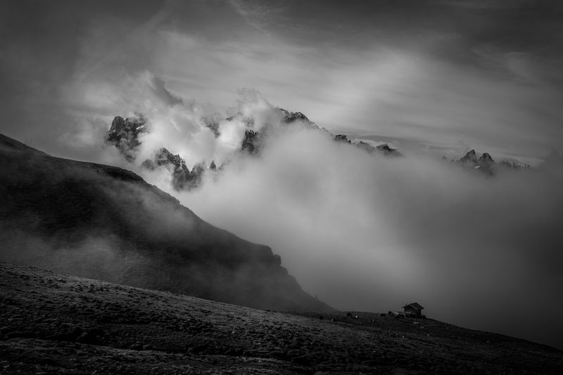 Black and white effect of dolomite peaks sprouting from the clouds at dawn, south tyrol, italy