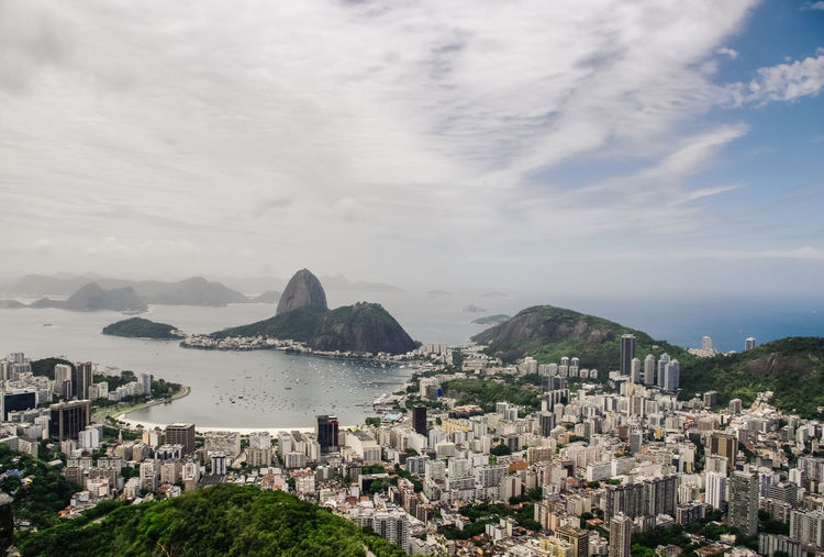 High Angle View Of Cityscape By Sugarloaf Mountain Against Cloudy Sky
