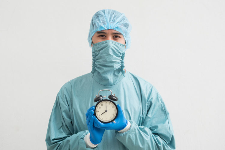 Portrait Of Surgeon Holding Alarm Clock While Standing Against White Background