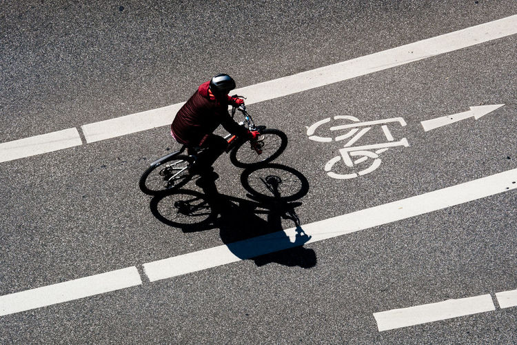 High Angle View Of Man Cycling On Bicycle Lane During Sunny Day