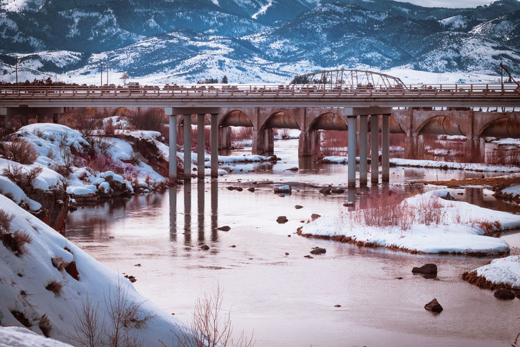 Bridge over river amidst snow covered land