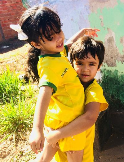 Portrait of brother carrying sister in yard