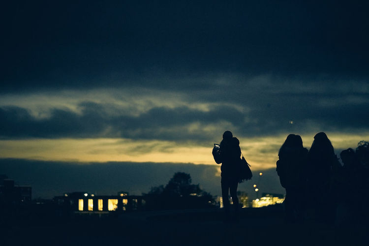 Silhouette people standing against cloudy sky during sunset