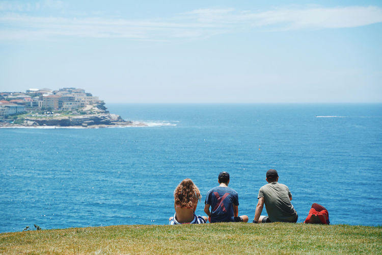 Tourist relaxing on bondi beach Water Sea Rear View Real People Sky Lifestyles Horizon Over Water Beauty In Nature Group Of People Horizon Nature Sitting Day Men Architecture Leisure Activity Togetherness Land People Outdoors Looking At View Australia Sydney Bondi Beach