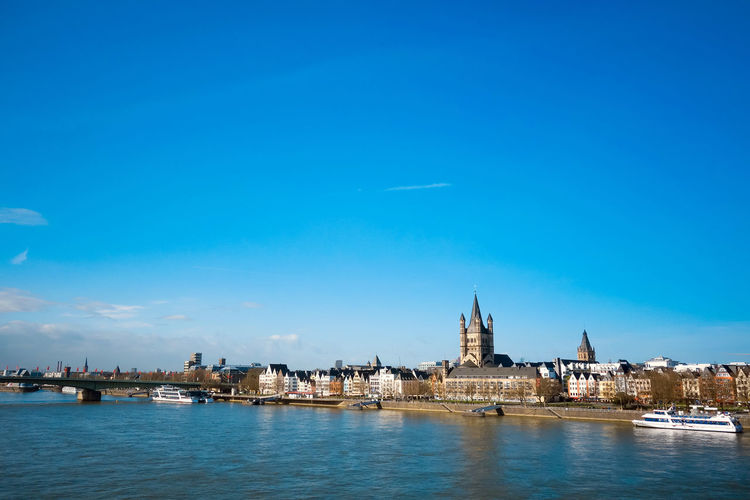Distant view of great st martin church by rhine river against blue sky