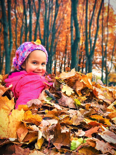Girl in autumn leaves during winter
