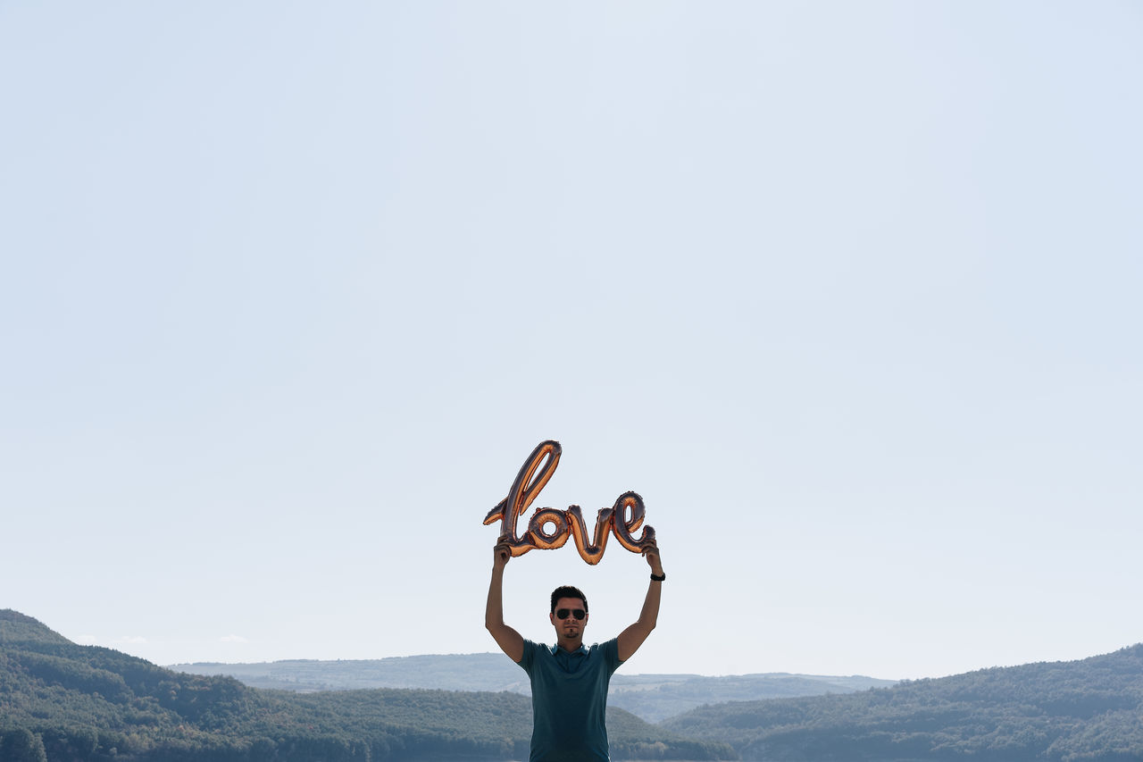 Man Holding Love Text Balloon Standing Against Clear Sky
