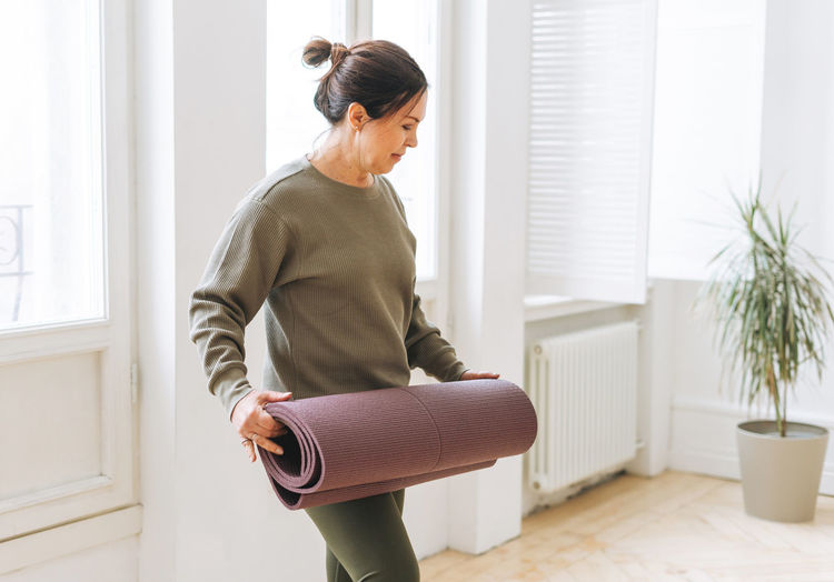Attractive middle aged brunette woman in sportswear with yoga mat in the light studio