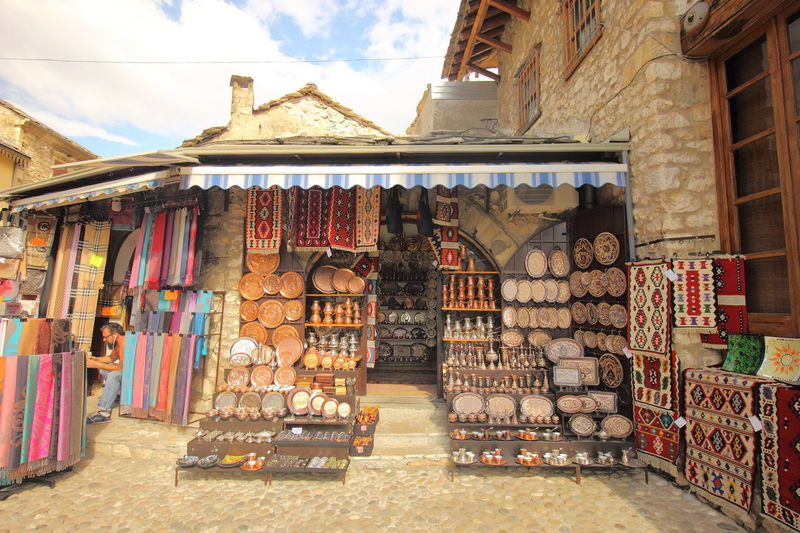 Shops in Mostar Old Town selling authentic Bosnian's craft of engraved copper plate and pot Bosnia And Herzegovina Mostar Mostar Bosnia Craft Engraved Metal Large Group Of Objects Multi Colored Shop Variation