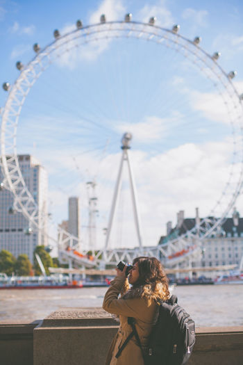 A tourist taking photos at the London Eye. Architecture City Cultures Day Ferris Wheel London London Eye London Lifestyle One Person One Woman Only Taking Photos Tourism Tourist Travel Destinations Adventures In The City #urbanana: The Urban Playground