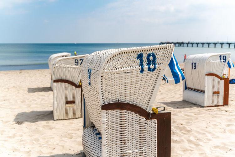 Beach chair on sand beach under blue sky and sunshine. german baltic sea beach scene.