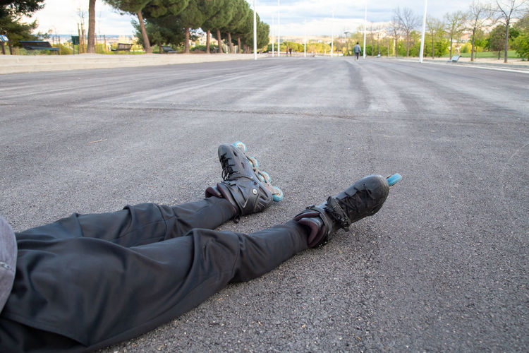 Low section of man lying on road