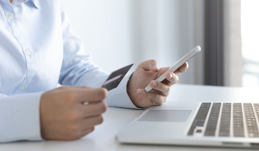 Midsection of businessman holding credit card while using smart phone for online shopping at office