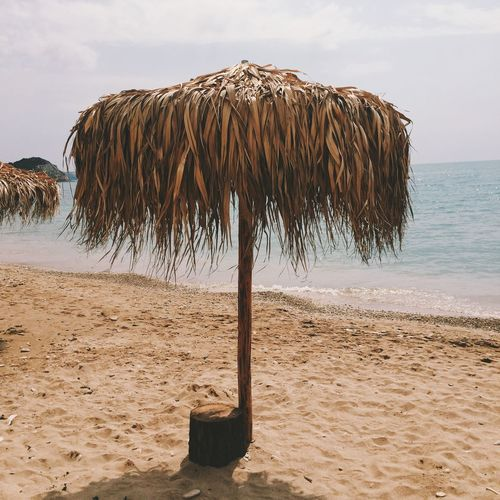 Thatched roof umbrella at beach on sunny day