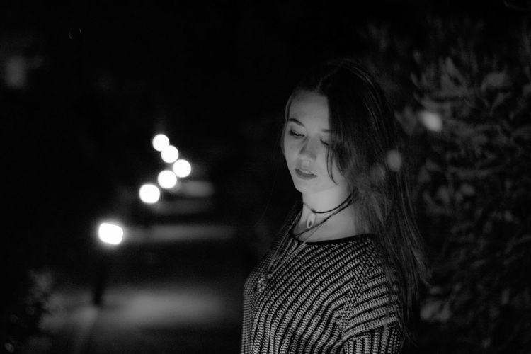 Young woman looking down at night