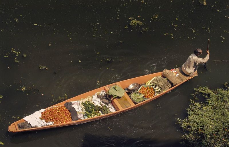 High angle view of man with vegetables in boat rowing on lake