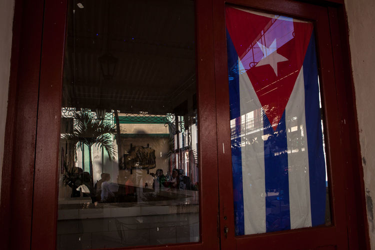 A national flag hangs on the windows of a café in Cienfuegos, Cuba. Cuba Cuban Flag National Flag NationalPride Pride Travel Travel Photography Window