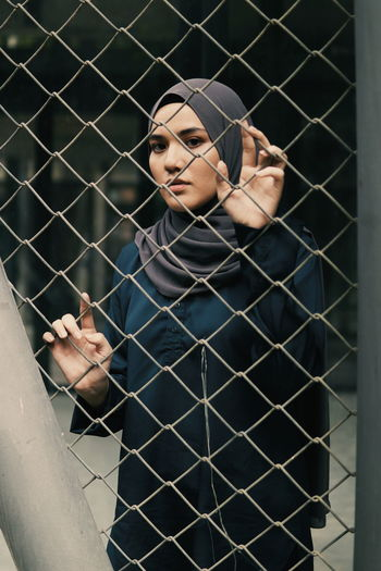 Portrait of serious young woman seen through chainlink fence