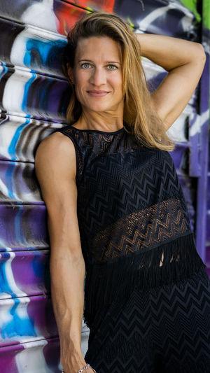 Portrait Of Confident Mature Woman Standing Against Shutter