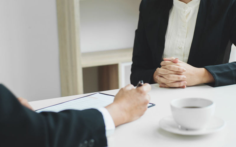 Midsection of colleagues by coffee cup on table