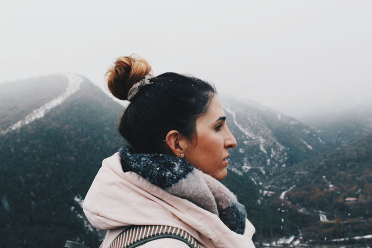 Side view of young woman standing in snow
