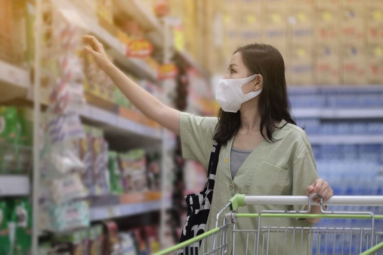 Full length of woman wearing mask at store
