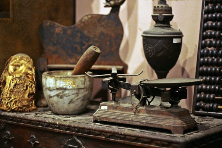 Rusty weighing scale and mortar and pestle on table
