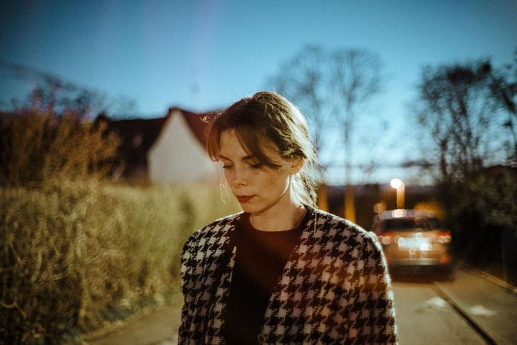 Portrait of teenage girl standing by tree against sky