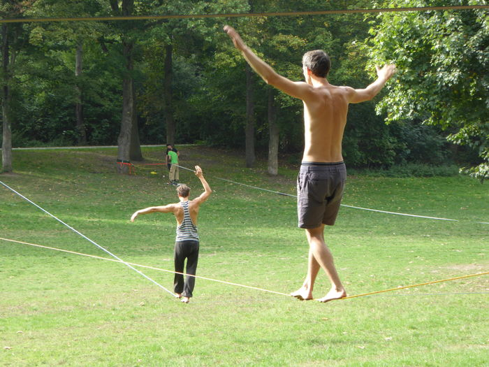 Arms Raised Balance Act Balancing Dont Fall! Full Length Grass Green Park Nature Outdoors Park Exersises Shirtless Slack Rope Walking Sports Tight Rope Walking Togetherness Two People Walking The Rope