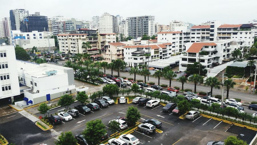 High angle view of cars parked at parking lot by traffic in city