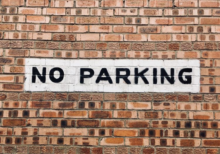 Close-up of no parking sign on brick wall